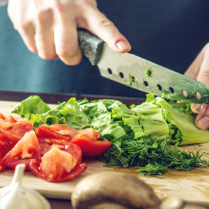 lettuce and tomatoes being cut up on chopping block