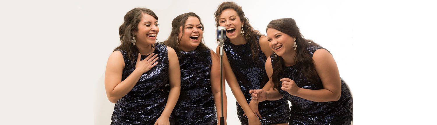four laughing women dressed in purple standing around a microphone