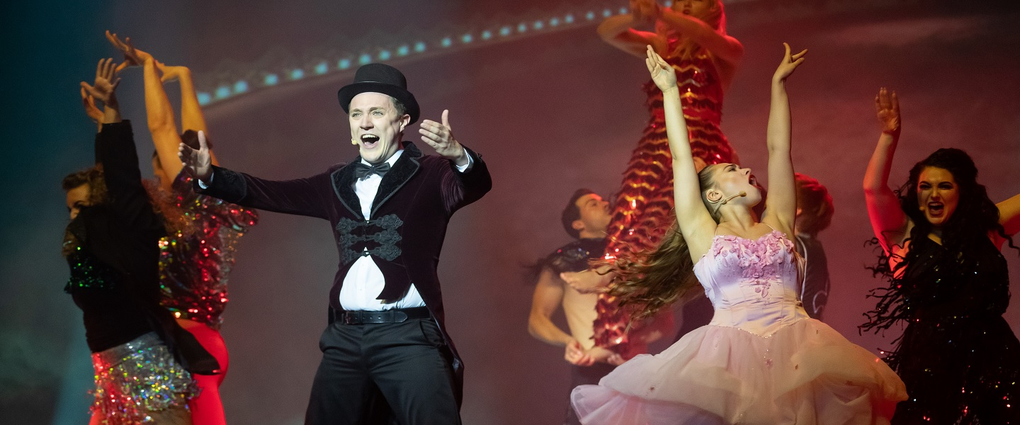 woman dressed in a suit and top hat and woman in ballet costume singing and dancing on stage