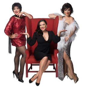 red chair with one woman sitting on it and two women standing, one on either side of the chair