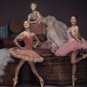 Four ballet dancers posed on pile of baskets and suitcases